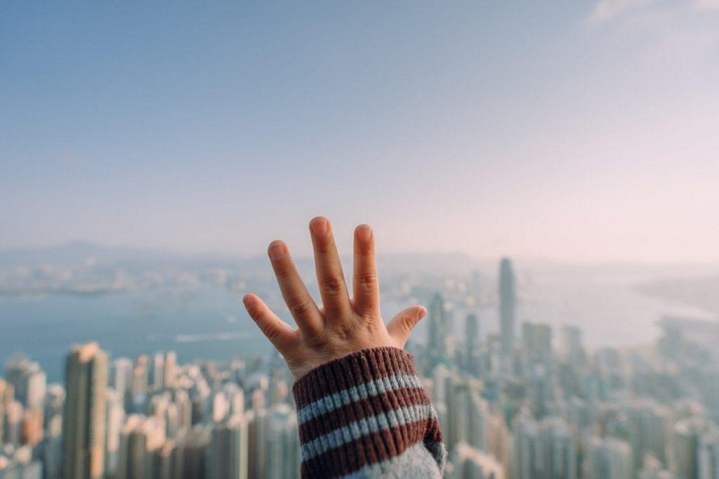Вид на місто з балкону багатоповерхівки, дитяча рука на фоні горизонту