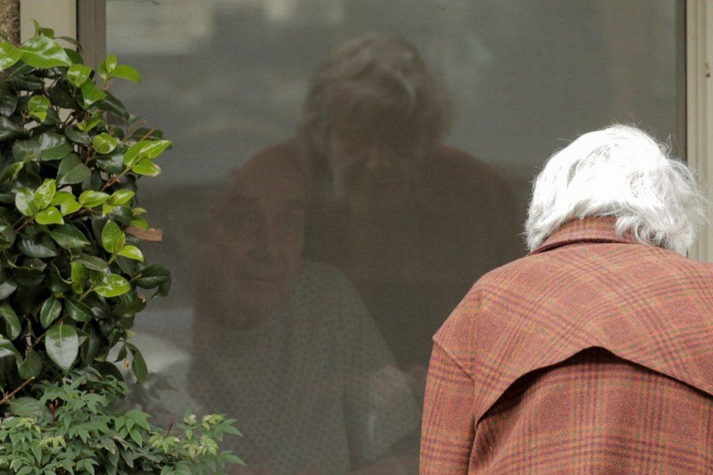 Коронавірус найбільш небезпечний для людей похилого віку. Стара жінка прийшла побачити свого чоловіка через вікно лікарні